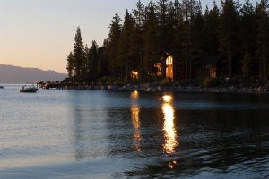 sunset over lake tahoe reflecting off the windows of a lakeside cabin